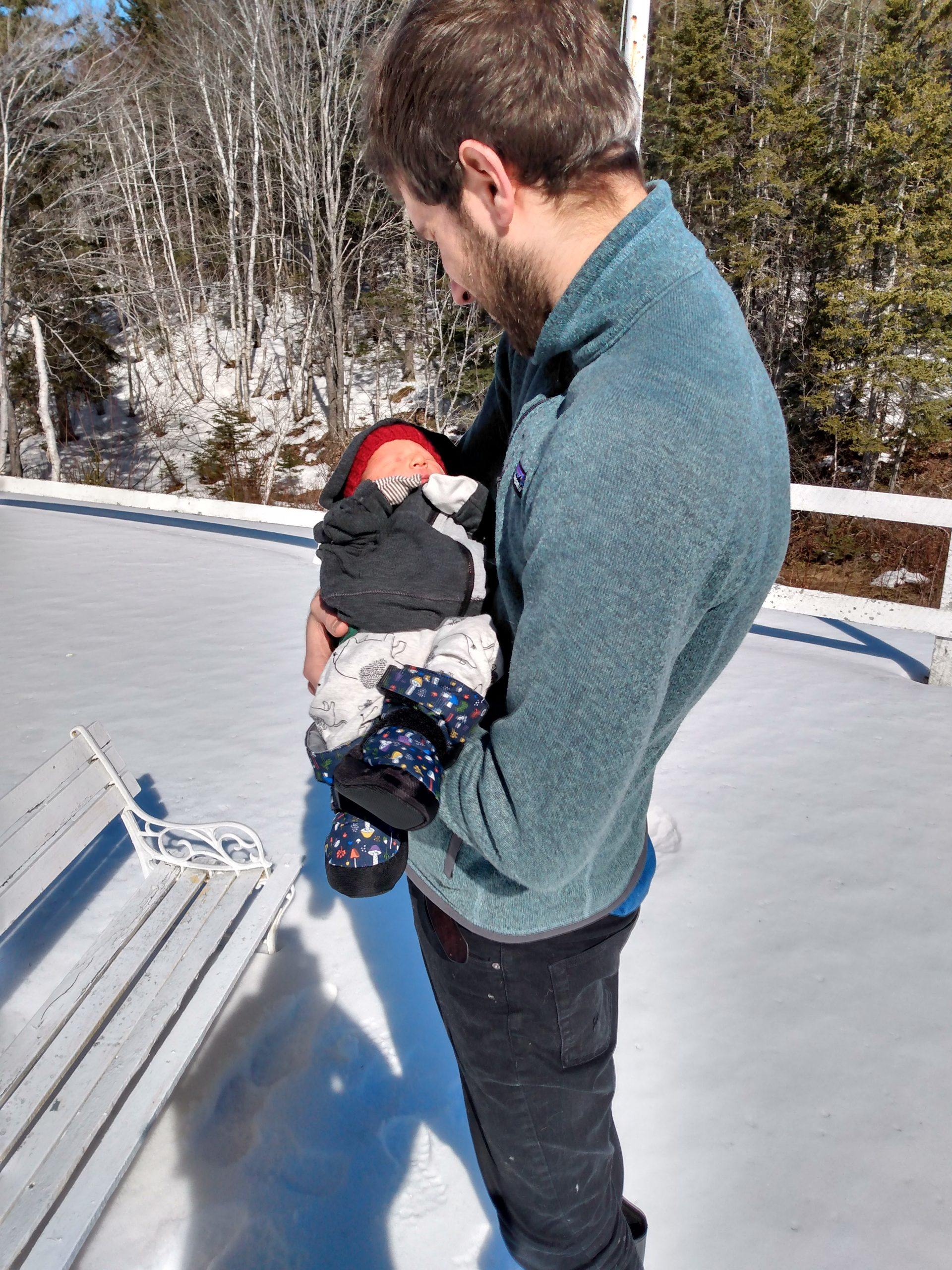 Josh standing outside in snow with his new baby.