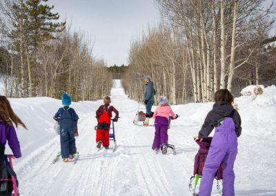 Photo of kids on kicksleds in winter.